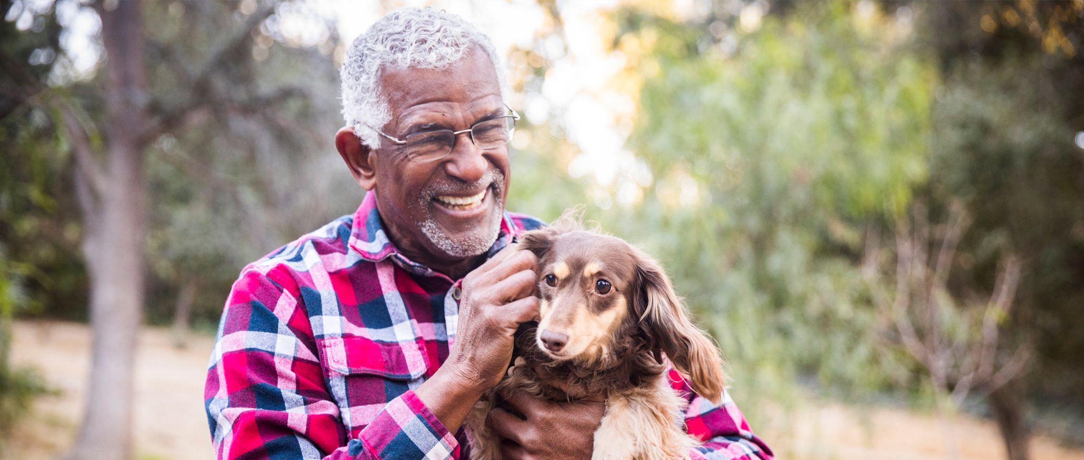 Older American Man Outdoors with Dog